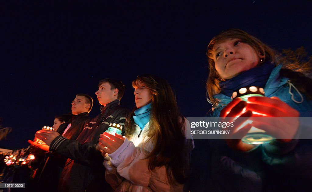 People hold candles at the monument to Chernobyl victims in Slavutich, some 50 kilometres (30 miles) from the accident site, and where many of the power station's personnel used to live, during a memorial ceremony early on April 26, 2013. Ukraine on April 26 marks the 27th anniversary of the Chernobyl disaster which was the world's worst nuclear accident.