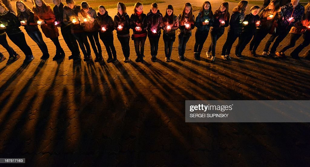 People hold candles at the monument to the Chernobyl victims in Slavutich, some 50 kilometres (30 miles) from the accident site, and where many of the power station's personnel used to live, during a memorial ceremony early on April 26, 2013. Ukraine on April 26 marks the 27th anniversary of the Chernobyl disaster plant disaster that contaminated large swaths of Europe and made the world rethink the benefits of the peaceful atom. AFP PHOTO / SERGEI SUPINSKY / AFP / SERGEI SUPINSKY
