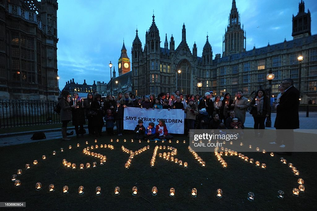 People hold candles during a candlelit vigil in central London on March 14, 2013 as part of global action on the second anniversary of the start of the Syria conflict. The UN food agency said that the challenge it is facing to feed millions of people in war-ravaged Syria has escalated as funds dry up two years into the conflict.