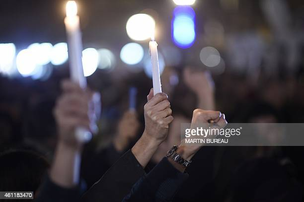 People hold candles during a gathering on the Place de Republique in Paris on January 8 in tribute to the twelve people killed the day before in an...