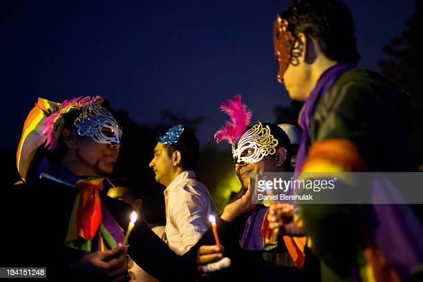 People hold candles during a vigil for those killed in a fire earlier in the week as they participate during the 4th Delhi Queer Pride 2011 March on...