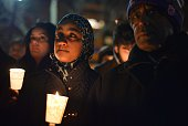 People hold candles during a vigil for three young Muslims killed in Chapel Hill North Carolina at DuPont Circle on February 12 2015 in Washington DC...