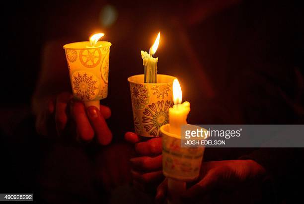 People hold candles during a vigil in Roseburg Oregon on October 1 for ten people killed and seven others wounded in a shooting at a community...