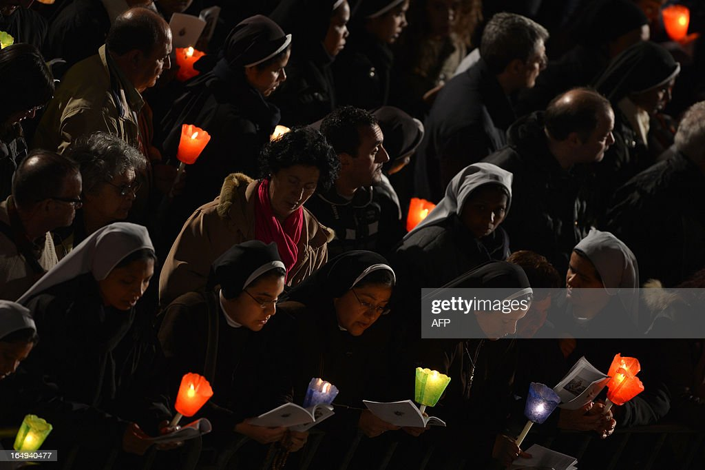 People hold candles during the celebration of the Way of the Cross on Good Friday on March 29, 2013 at the Colosseum in Rome. Pope Francis presided over his first Good Friday which will culminate in a torch-lit procession at Rome's Colosseum and prayers for peace in a Middle East 'torn apart by injustice and conflicts'.