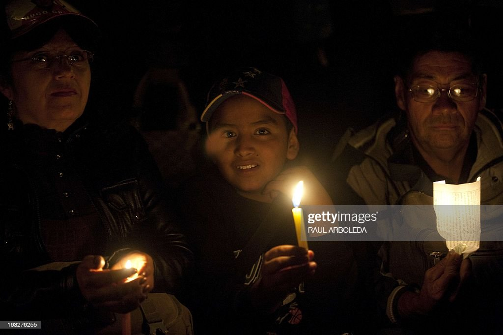 People hold candles outside the Venezuelan embassy in Bogota, Colombia on March 6, 2013, after Venezuelan President Hugo Chavez's death. The flag-draped coffin of Venezuelan leader Hugo Chavez was borne through throngs of weeping supporters on Wednesday as a nation bade farewell to the firebrand leftist who led them for 14 years. AFP PHOTO / Raul ARBOLEDA