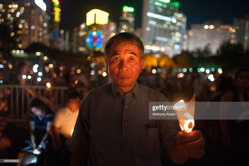 People hold candles to commemorate the 25th anniversary of the Tiananmen Square events during a candlelight vigil at Victoria Park on June 4 2014 in...
