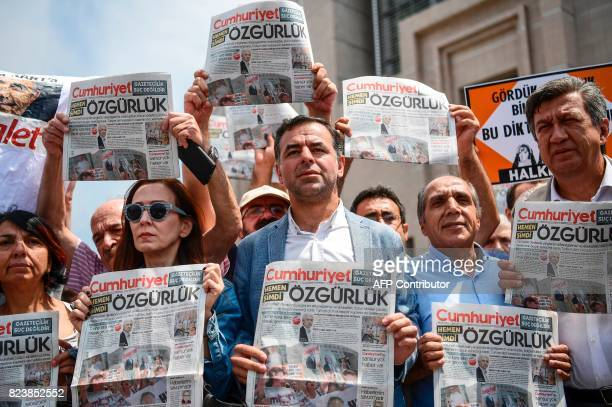 People hold copies of today's Cumhuriyet daily newspaper on July 28 2017 during a demonstration in front of Istanbul's courthouse A Turkish court was...
