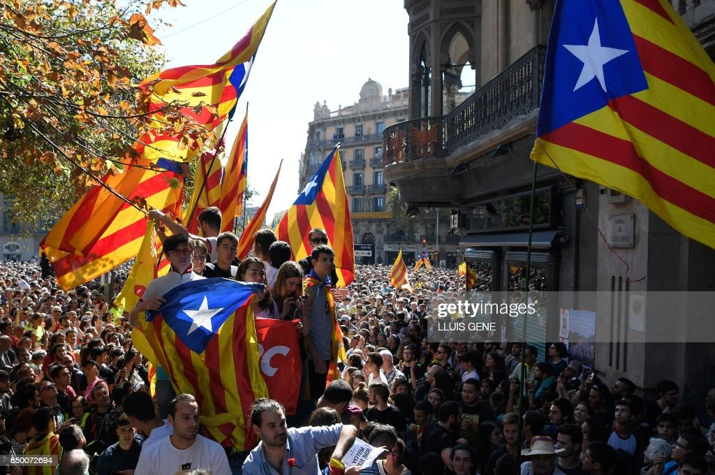 TOPSHOT - People hold 'Esteladas' (Catalan pro-independence flag) during a protest at the entrance of Catalonia's regional government economy headquarters in Barcelona on September 20, 2017. Thousands took to the streets of Barcelona as Spanish police detained 13 Catalan government officials in a crackdown ahead of an independence referendum which Madrid says is illegal. With tensions mounting, separatist organisations called for more people to protest as leaders in the northeastern region pressed ahead with preparations for the October 1 vote despite Madrid's ban and a court ruling deeming it unconstitutional. GENE