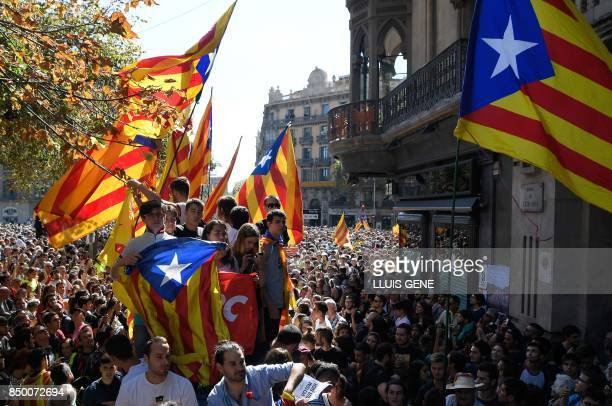 TOPSHOT People hold 'Esteladas' during a protest at the entrance of Catalonia's regional government economy headquarters in Barcelona on September 20...