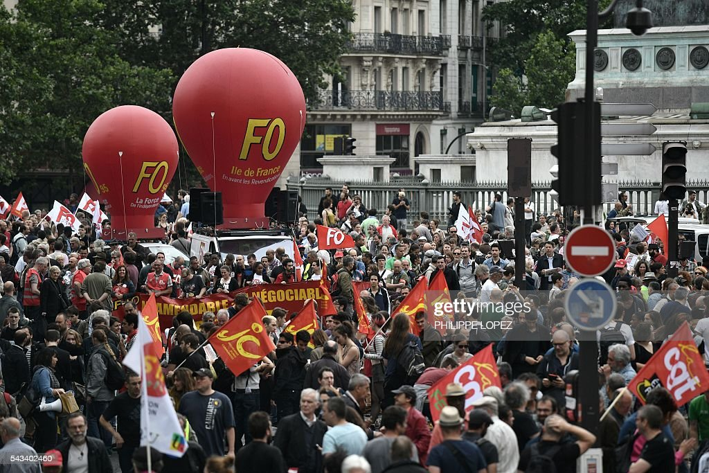 People hold flags and banners during a demonstration against controversial labour reforms, on June 28, 2016 on Bastille Square in Paris. Unions have called repeated strikes and marches in opposition to the law, which seeks to bring down France's intractable 10-percent unemployment rate by making it easier to hire and fire workers. / AFP / PHILIPPE
