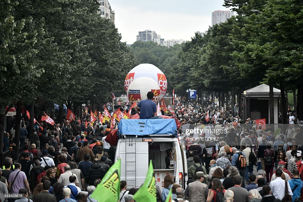 People hold flags during a demonstration against controversial labour reforms, on June 28, 2016 on Bastille Square in Paris. Unions have called repeated strikes and marches in opposition to the law, which seeks to bring down France's intractable 10-percent unemployment rate by making it easier to hire and fire workers. / AFP / PHILIPPE