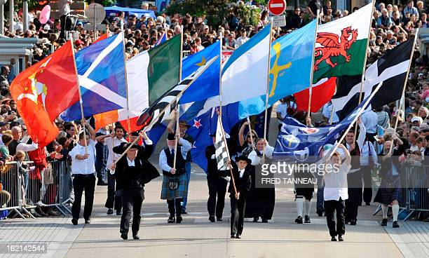 People hold flags of Celtic countries and regions perform a traditional Breton dance on August 7 2011 in Lorient during the celtics nations Great...