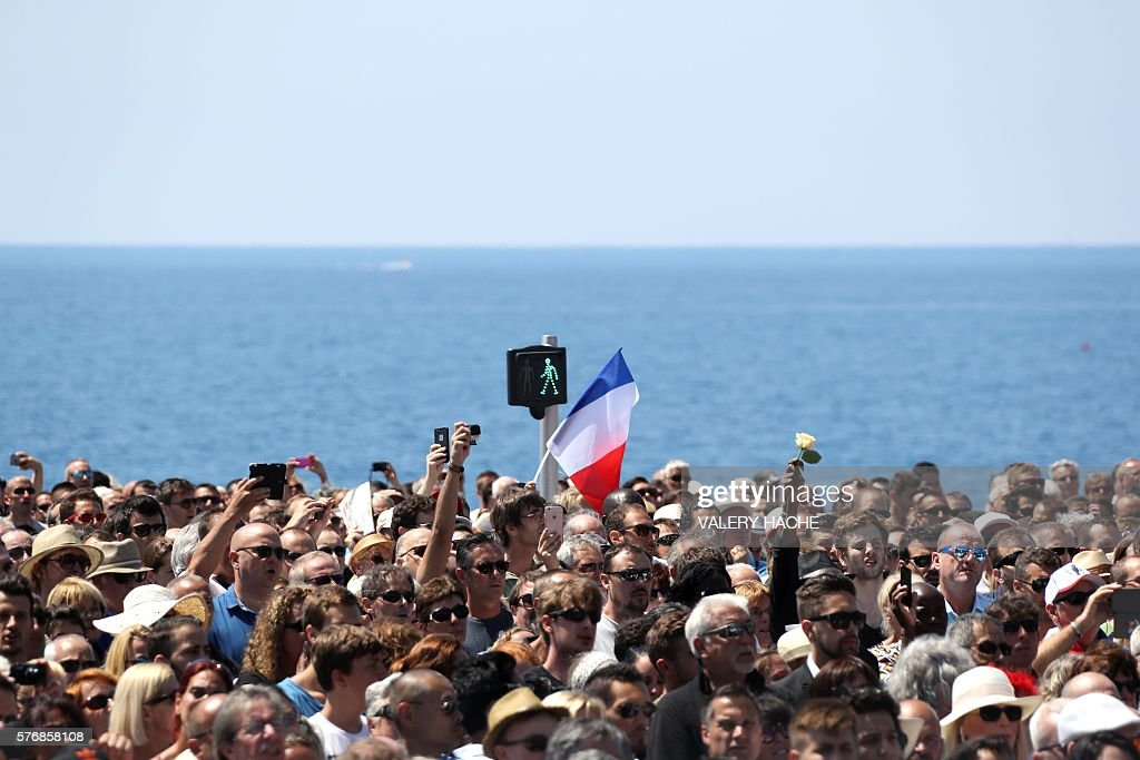 TOPSHOT - People hold flowers and French flags as they gather to observe a minute's silence in front of the Jardin Albert 1er on the Promenade des Anglais seafront in Nice, on July 18, 2016, in tribute to the victims of the deadly Nice attack on Bastille day. France was set to hold a minute's silence on July 18, 2016 to honour the 84 victims of the Nice truck attack, but a period of national mourning was overshadowed by bickering politicians. Church bells will toll across the country, and the country will fall silent at midday, a now grimly familiar ritual after the third major terror attack in 18 months on French soil. / AFP / Valery HACHE