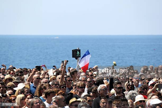 TOPSHOT People hold flowers and French flags as they gather to observe a minute's silence in front of the Jardin Albert 1er on the Promenade des...