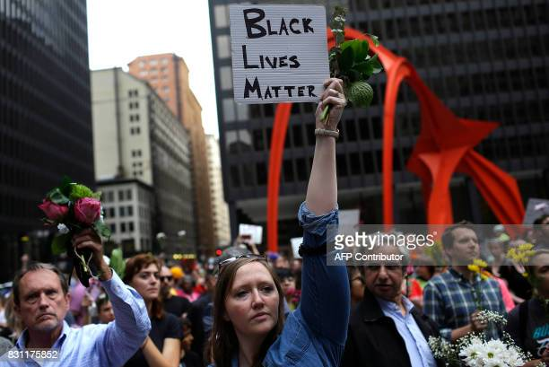 People hold flowers at a vigil August 13 2017 in Chicago Illinois for the victims in the previous day's violent clashes in Charlottesville Virginia...