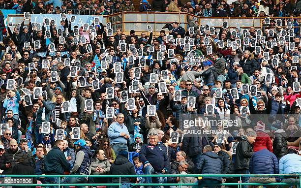 People hold flyers depicting the face of Napoli's French defender Kalidou Koulibaly before the Italian Serie A football match SSC Napoli vs Carpi FC...