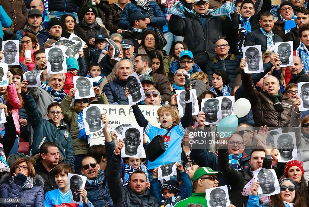 People hold flyers depicting the face of Napoli's French defender Kalidou Koulibaly before the Italian Serie A football match SSC Napoli vs Carpi FC on February 7, 2016 at the San Paolo stadium in Naples, in solidarity with the player victim of racists slogans from Lazio's fans during the football match SS Lazio vs SSC Napoli on February 3. / AFP / CARLO HERMANN