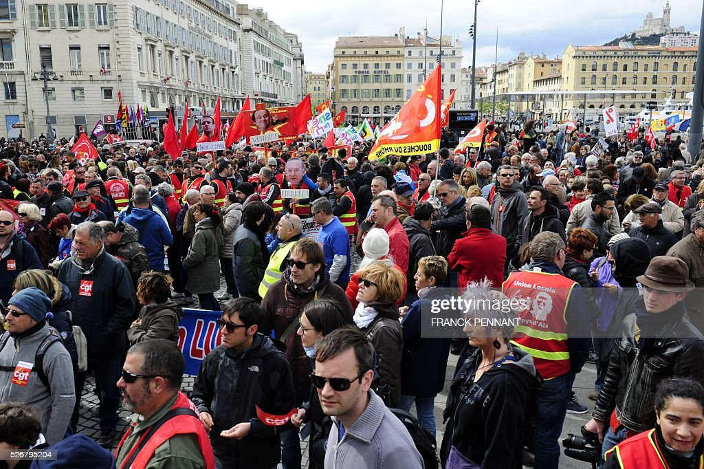 People hold French CGT Trade Union's flags as they demonstrate in the streets of Marseille during the traditional May Day rally on May 1, 2016. / AFP / Franck PENNANT