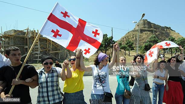 People hold Georgian flags during a rally marking the second anniversary of Georgia's violent conflict with Russia over the breakaway region of South...