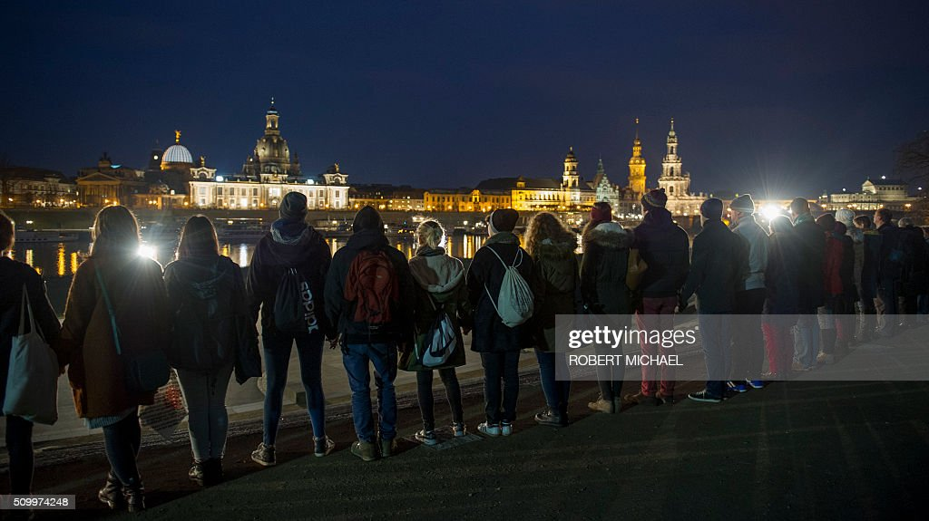 People hold hands as they create a human chain along the Elbe river in front of the Dresden historical city center to commemorate the 71st anniversary of the bombing of Dresden on February 13, 2016. A massive bombing raid by Allied forces on Dresden beginning on February 13, 1945 sparked a firestorm that destroyed much of the historical centre of the city. / AFP / Robert MICHAEL