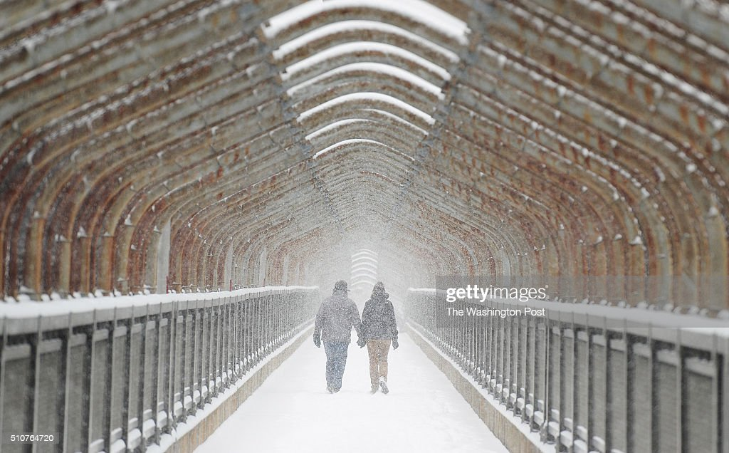 People hold hands as they cross a pedestrian bridge spanning Interstate 395 on Monday February 15 2016 in Arlington VA Snow returned to the...