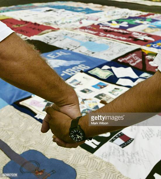People hold hands while standing at the AIDS Memorial Quilt June 25 2004 in Washington DC The quilt consists of more than 45000 panels pieced...
