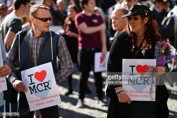 People hold 'I love MCR' banners as they arrive to attend a vigil in Albert Square in Manchester northwest England on May 23 in solidarity with those...