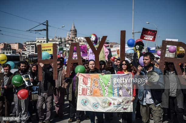 TOPSHOT People hold letters reading 'No' and shout slogans as they march over the Galata bridge on April 2 in Istanbul during a protest against the...