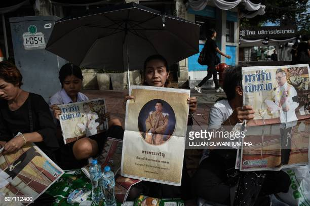 TOPSHOT People hold newspaper images of Thailand's new King Maha Vajiralongkorn outside the Grand Palace in Bangkok on December 2 2016 Crown Prince...