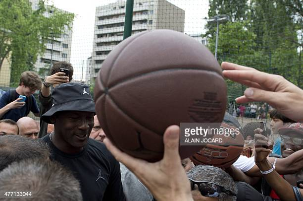 People hold out basketball to receive autographs as US former basketball player Michael Jordan leaves after the inauguration of a street basketball...