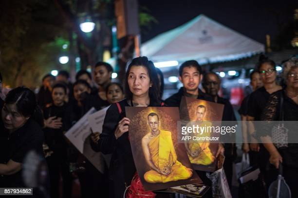 People hold painted portraits of Thailand's late king as they and others leave the Grand Palace in Bangkok on October 5 after mourning him in the...