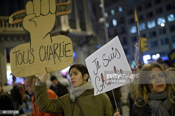 People hold pencils and placards reading 'I Am Charlie' outside the Consulate of France in Barcelona on January 9 2015 during a tribute for victims...