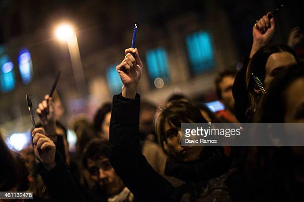 People hold pencils up during a gathering of people showing their support for the victims of the terrorist attack at French magazine Charlie Hebdo in...