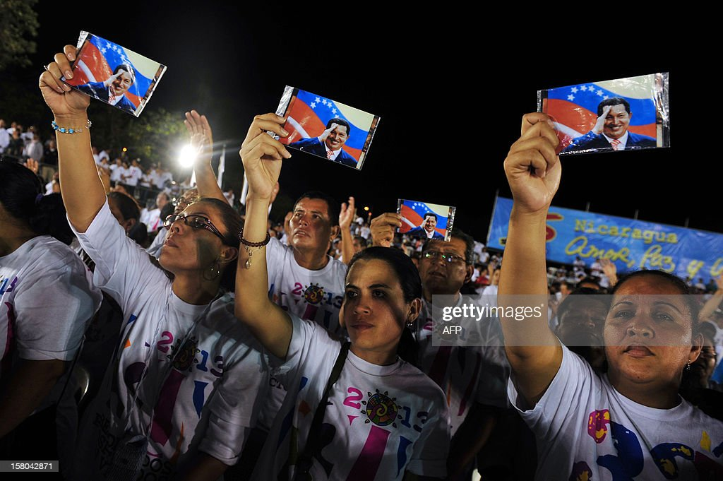 People hold photographs of Hugo Chavez during a ceremony held in Managua to pray for the health of Hugo Chavez, on December 09, 2012. AFP PHOTO / Hector RETAMAL