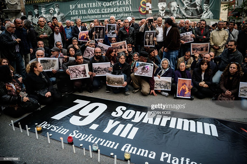 People hold pictures depicting killed victims of Dersim massacre between 1936 and 1939, behind a placard reading 79th anniversary of the genocide during a demonstration on May 4, 2016 in Istanbul. Air strikes and ground operations in the city of Dersim (now named Tunceli) killed 13,800 people between 1936 and 1939, according to an official document Erdogan said in 2011 / AFP / OZAN