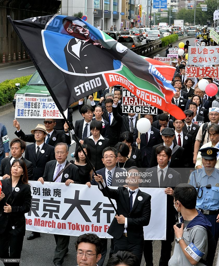 People hold placards against racism as they take place in a march in Tokyo on September 22, 2013. Some 2,000 people took part in an anti-discrimination rally to commemorate the 50th anniversary of the March on Washington and Martin Luther King Jr.'s 'I have a dream' speech on August 28, 1963. AFP PHOTO / Yoshikazu TSUNO