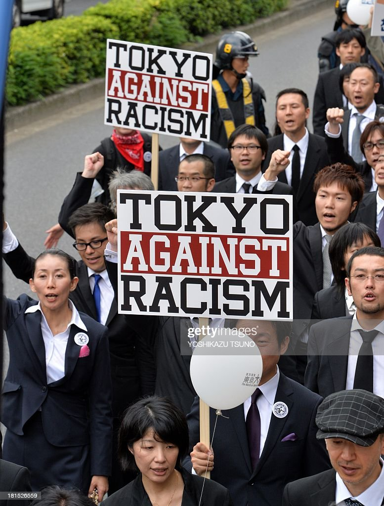 People hold placards against racism at a demonstration in Tokyo on September 22, 2013. Some 2,000 people took part in an anti-discrimination rally to commemorate the 50th anniversary of the March on Washington and Martin Luther King Jr.'s 'I have a dream' speech on August 28, 1963. AFP PHOTO / Yoshikazu TSUNO