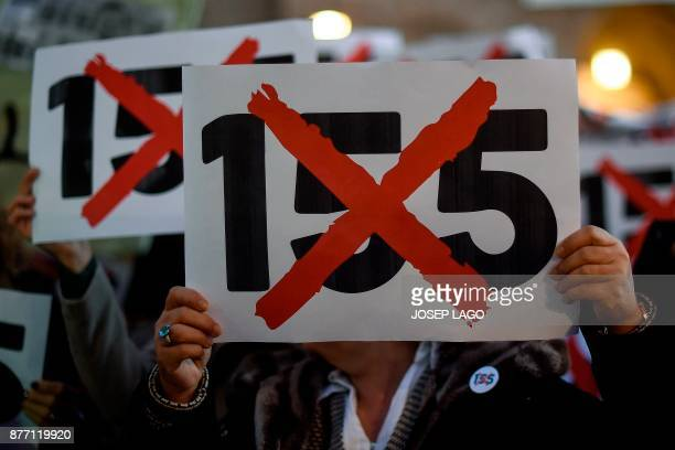 TOPSHOT People hold placards against the Article 155 of the Spanish constitution which Madrid has used to impose direct rule over the semiautonomous...