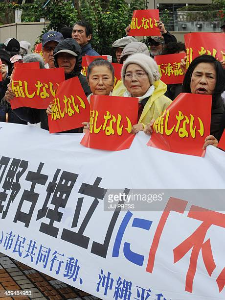 People hold placards and a banner during a rally denouncing the relocation of a US military base in front of the Okinawa prefectural office in Naha...