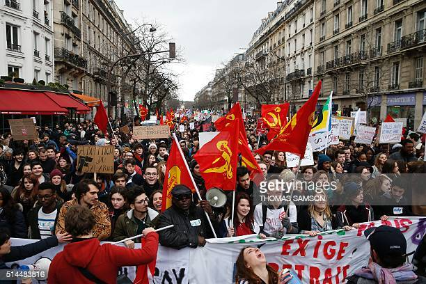 People hold placards and flags as they take part in a demonstration called by youth organisations and students' unions on March 9 in Paris during a...