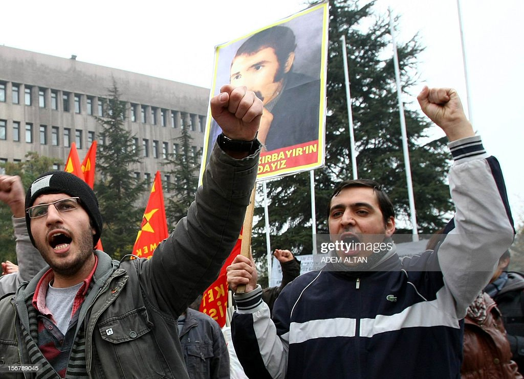 People hold placards and flags during a demonstration outside the courthouse as the trial of the two surviving leaders of Turkey's 1980 military coup continues in Ankara, on November 21, 2012. Kenan Evren, 94, who served as president after the military takeover, and Tahsin Sahinkaya, 86, the former air force commander defended today their takeover as 'patriotism,' on the second day of a landmark trial where they again appeared by video link.. Some 300 people demonstrated Tuesday outside the Ankara court urging authorities to severely punish the two retired generals.