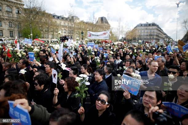 People hold placards and white roses as they gather on the Place de la Republique in Paris on April 2 2017 to protest after the death of Liu Shaoyo a...