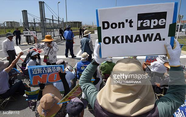 People hold placards as they protest against the presence of US bases in front of the gate of the US Marine Corps' Camp Schwab in Nago on the...