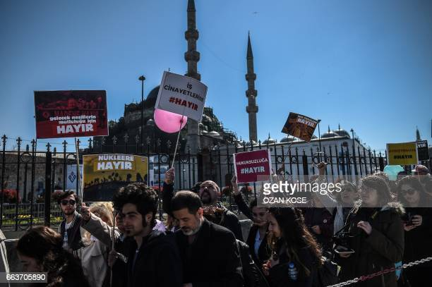 People hold placards calling Turkish voters to vote 'no' on the upcoming referendum as they shout slogans while they march from the Galata bridge to...