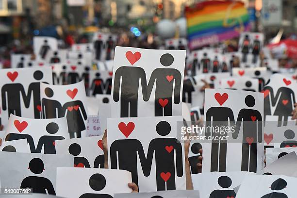 People hold placards depicting hearts and couples during a flash mob for the annual Lesbian Gay Bisexual and Transgender Pride Parade in Milan on...