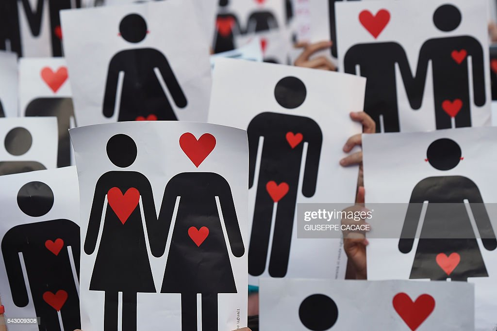 People hold placards depicting hearts and couples, during a flash mob for the annual Lesbian, Gay, Bisexual and Transgender (LGBT) Pride Parade in Milan, on June 25, 2016. / AFP / GIUSEPPE