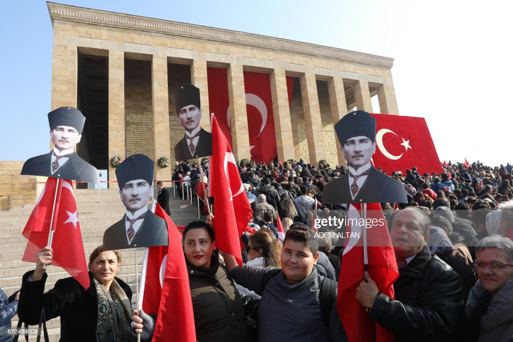 People hold placards depicting Mustafa Kemal Ataturk, founder of modern Turkey, and Turkish national flag as they arrive to attend a ceremony marking the 79th death anniversary of Ataturk at his mausoleum called Anitkabir, in Ankara, on November 10, 2017. /