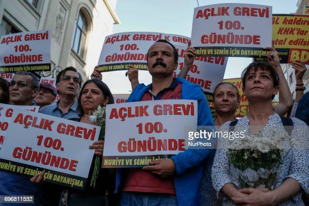 People hold placards during a protest in support of sacked academic Nuriye Gulmen and primary school teacher Semih Ozakca who were arrested by a...