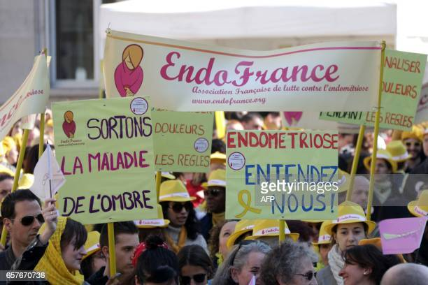 People hold placards during a rally organised as part of the 4th edition of the 'Worldwide Endometriosis March' to help raise awareness of...