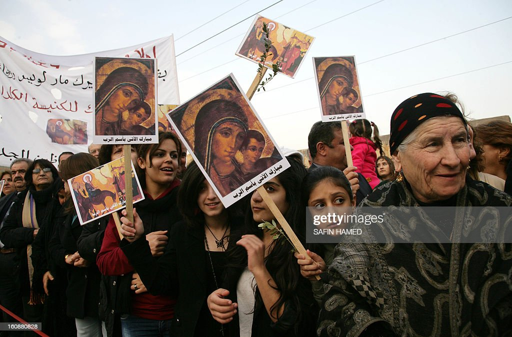People hold placards featuring icons during a ceremony marking the return to Iraq from the Vatican of the new patriarch of the Iraq-based Chaldean Church, Louis Sako, on February 7, 2013 at Saint Joseph's Cathedral in the northern Kurdish city of Ainkawa. Louis Sako, who replaced Emmanuel III Delly, will take the official title of Patriarch of Babylon of the Chaldeans. AFP PHOTO SAFIN HAMED